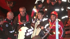 A passenger from South Korea, center, walks with Italian Firefighters after being rescued from the luxury cruise ship Costa Concordia which ran aground the tiny Tuscan island of Giglio, Italy, Sunday, Jan. 15, 2012. (AP Photo/Gregorio Borgia)