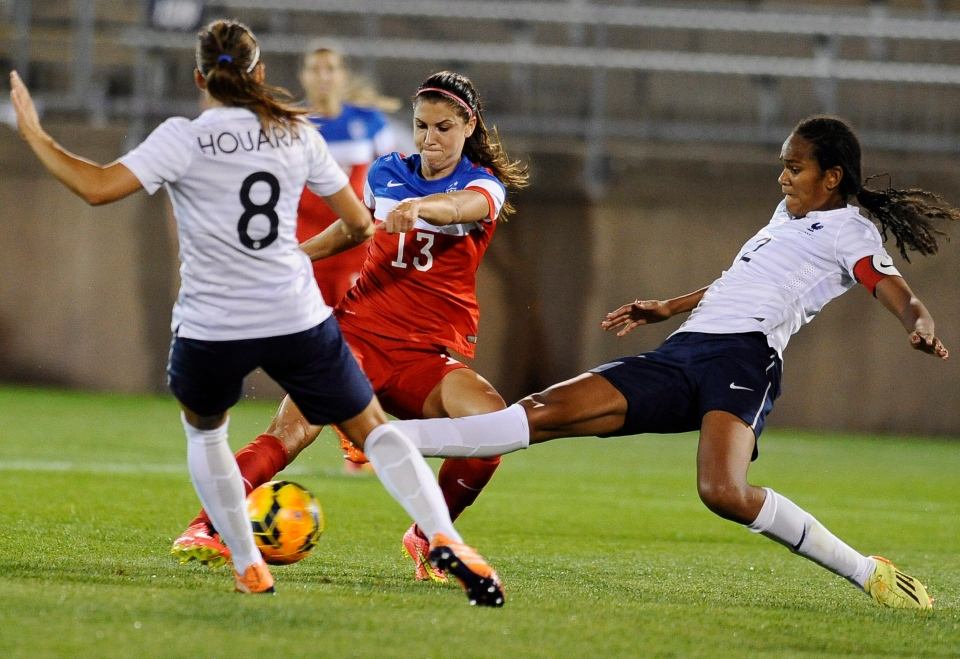 United States' Alex Morgan, centre, kicks a goal as France's Jessica Houara, left, and Wendie Renard, right, defend, during the second half of a women's friendly soccer match in East Hartford, Conn.  on Thursday, June 19, 2014.  (AP / Jessica Hill)