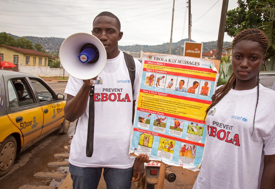 A man and woman taking part in a Ebola prevention campaign holds a placard with an Ebola prevention information message in the city of Freetown, Sierra Leone, Wednesday, Aug. 6, 2014. (AP / Michael Duff)
