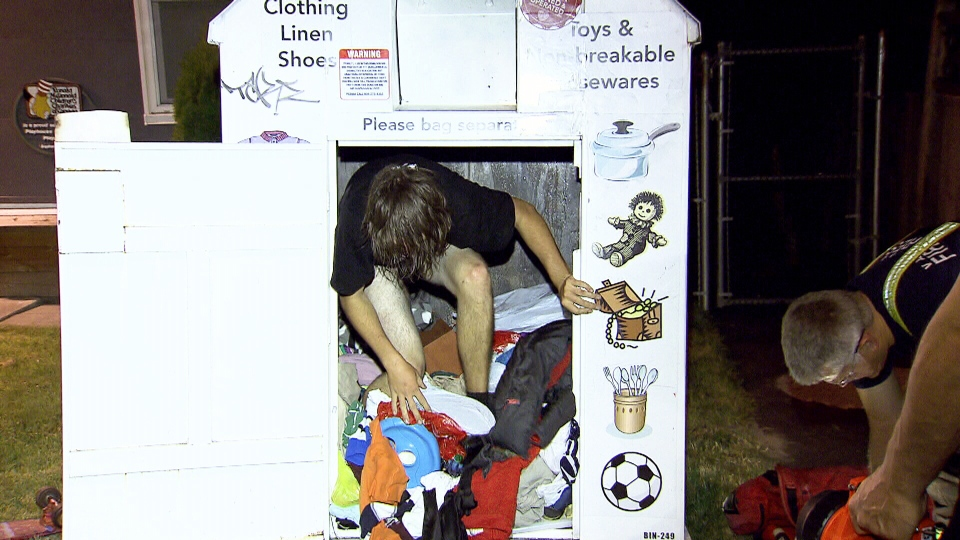 A man emerges from a clothing donation bin after emergency crews worked for 30 minutes to cut the container open on August 7, 2014.