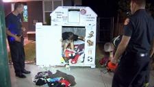 man stuck in clothing donation box
