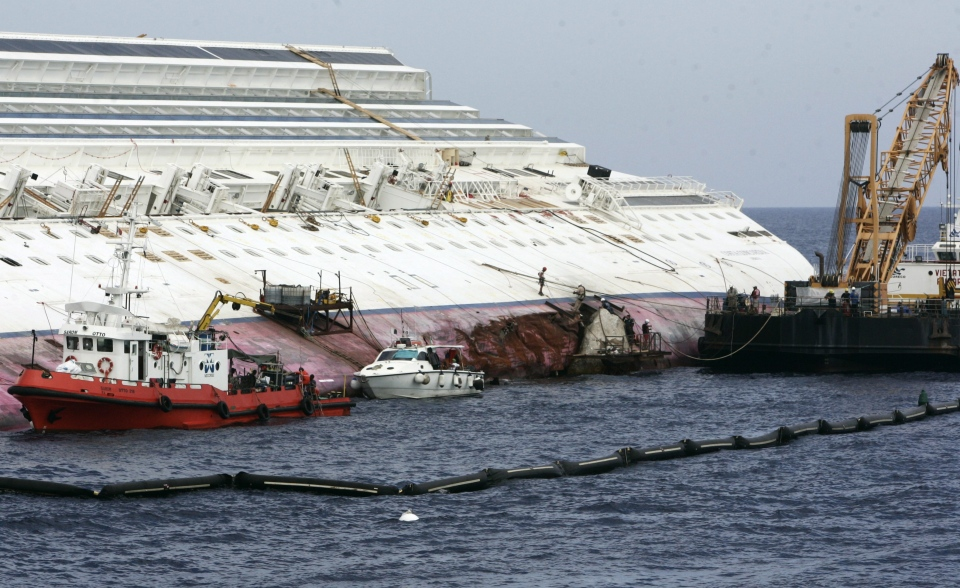Workers begin to remove the tons of rocky reef embedded into the Costa Concordia cruise ship's hull, a first step in plans to eventually tow the wreck away from the Giglio Island, Italy, where it ran aground last January, Thursday, July 12, 2012. (AP / Gregorio Borgia)