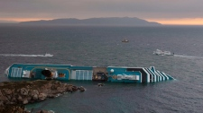 The Costa Concordia cruise liner lies on its side two days after it ran aground off the tiny Tuscan island of Giglio, Italy, Monday, Jan. 16, 2012. (AP / Gregorio Borgia)