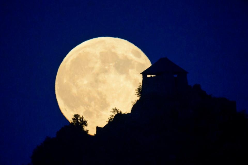 A 'Supermoon' full moon rises above the castle of Somoskoujfalu, in Hungary, late Saturday, July 12, 2014. (AP/MTI,Peter Komka)