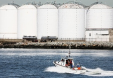 A U.S. Coast Guard boat passes fuel oil storage tanks on Wednesday, Aug. 27, 2008. The brief respite for consumers at the pump may soon come to an abrupt end as preparations for tropical storm Gustav curtail refining activity near the U.S. coast. (AP /Mark Lennihan)