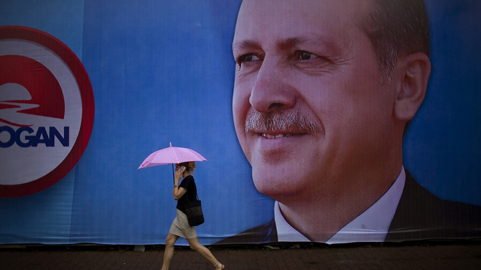 A woman talks on her phone as she walks past a poster of Prime Minister and presidential candidate in Turkey's Aug. 10 presidential election, Recep Tayyip Erdogan in downtown Istanbul, Turkey, Friday, Aug. 8, 2014. (AP / Emilio Morenatti)