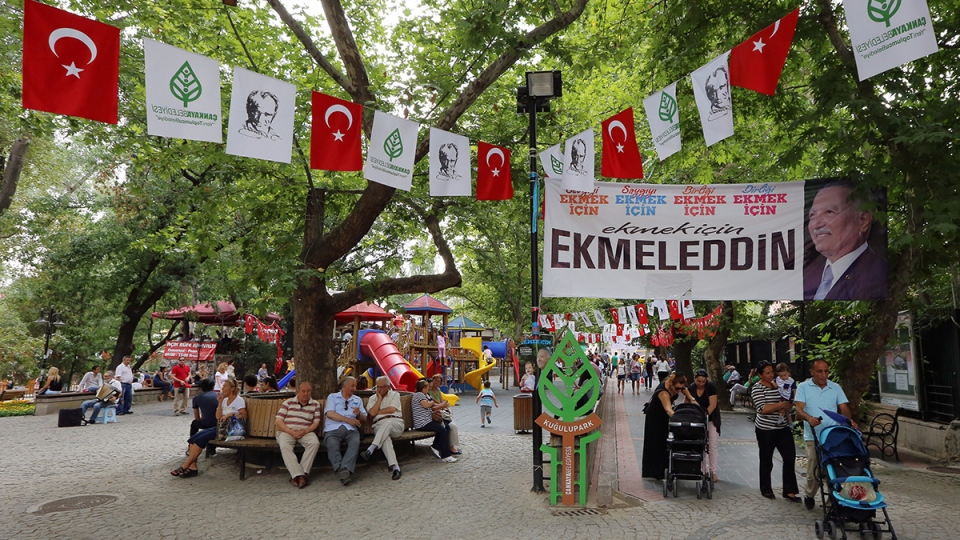 "People walk by a poster of the main opposition candidate in Turkey's Aug. 10 presidential election, Ekmeleddin Ihsanoglu, that reads ""to sow peace, love, respect and unity"" in Ankara, Turkey, Friday, Aug. 8, 2014. (AP / Burhan Ozbilici)"