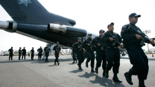 In this 2008 photo, federal police agents arrive at the main airport in Culiacan, Mexico. (AP / Miguel Tovar)