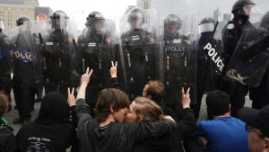 Two activists kiss while protesting in front of a line of riot police during the G20 Summit in Toronto Saturday, June 26, 2010. (Darren Calabrese / THE CANADIAN PRESS)