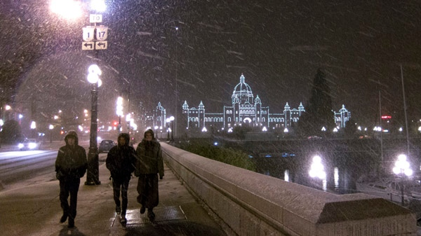 Pedestrians are seen walking along the sidewalk as the B.C. Legislature is lit up in the background during a heavy wet snowfall in downtown Victoria, B.C. Monday, Jan. 16, 2012. (Jonathan Hayward / THE CANADIAN PRESS)