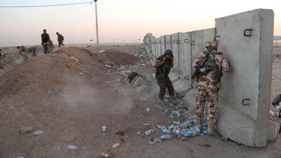 Kurdish Peshmerga fighters take cover during airstrikes targeting Islamic State militants near the Khazer checkpoint outside of the city of Irbil in northern Iraq, Friday, Aug. 8, 2014. (AP / Khalid Mohammed)