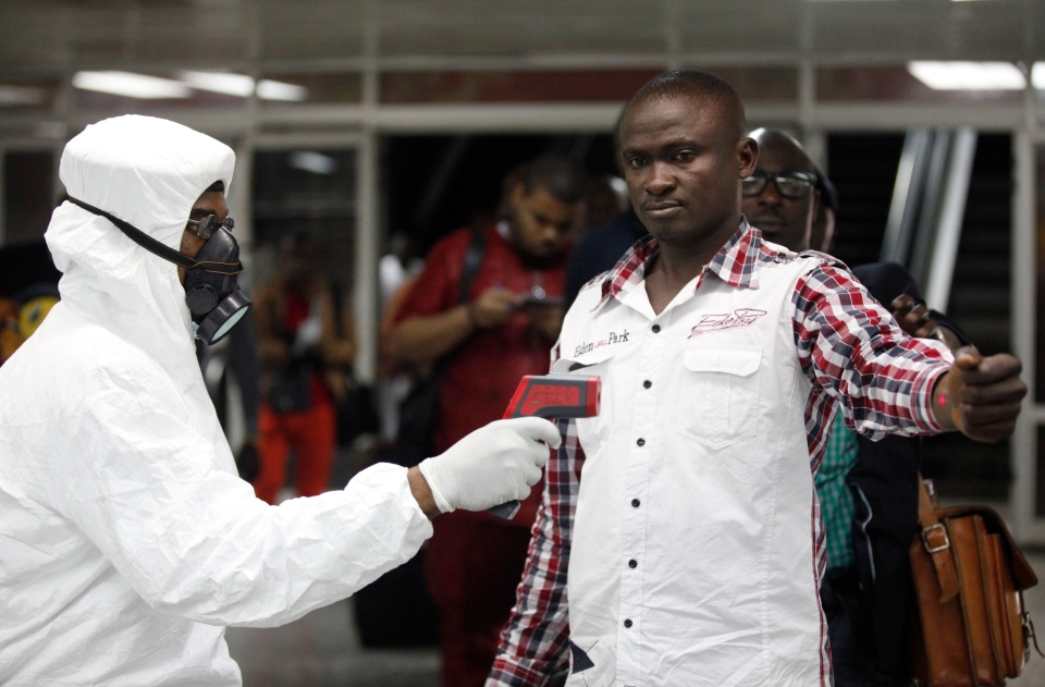 A Nigerian port health official uses a thermometer on a worker at the arrivals hall of Murtala Muhammed International Airport in Lagos, Nigeria, on Aug. 6, 2014. (AP/Sunday Alamba, File)