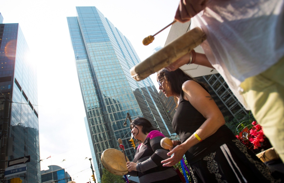 Members of the Secwepemc Women Warrior Society sing and beat drums while protesting against Imperial Metals outside of the Toronto Stock Exchange in Toronto's financial district on Thursday, Aug. 7, 2014. (Darren Calabrese / THE CANADIAN PRESS)