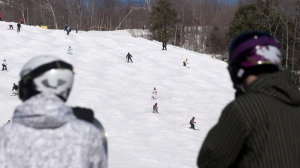 Skiers, wearing helmets, watch as others finish a day on the slopes at Mont Tremblant, on Thursday, March 19, 2009.  (Peter McCabe / THE CANADIAN PRESS)