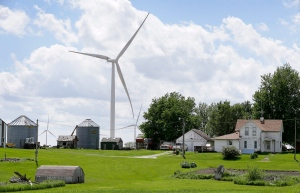 A wind turbine stands over a farm house on Monday, June 2, 2014, in Adair, Iowa. (AP /Charlie Neibergall)