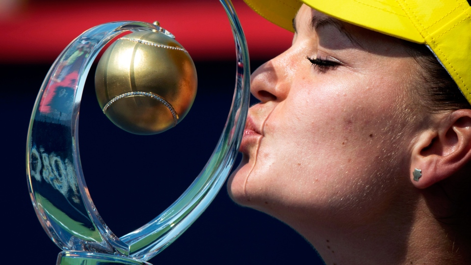 Agnieszka Radwanska of Poland kisses the winner's trophy after beating Venus Williams of the United States in the final at the Rogers Cup tennis tournament Sunday Aug. 10, 2014 in Montreal. (Paul Chiasson / THE CANADIAN PRESS)
