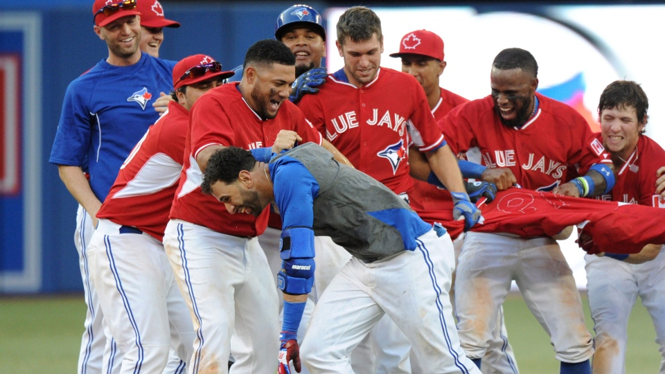 Toronto Blue Jays' Jose Bautista, center, celebrates with teammates after hitting a walk off single against the Detroit Tigers during the 19th inning in Toronto on Sunday August 10, 2014. (Jon Blacker / THE CANADIAN PRESS)