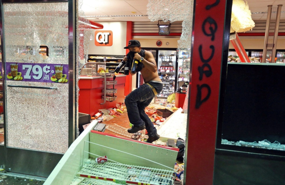 A man leaves a store in Ferguson, Mo. on Sunday, Aug. 10, 2014. (AP / St. Louis Post-Dispatch, David Carson)