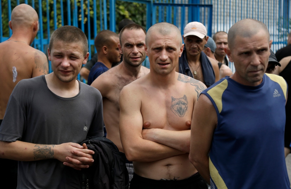 Inmates at a high-security facility stand in a yard after shelling in Donetsk, eastern Ukraine, Monday, Aug. 11, 2014. Local authorities say more than 100 prisoners have fled from a high-security facility after it was hit by shelling in the rebel stronghold of Donetsk. (AP / Sergei Grits)