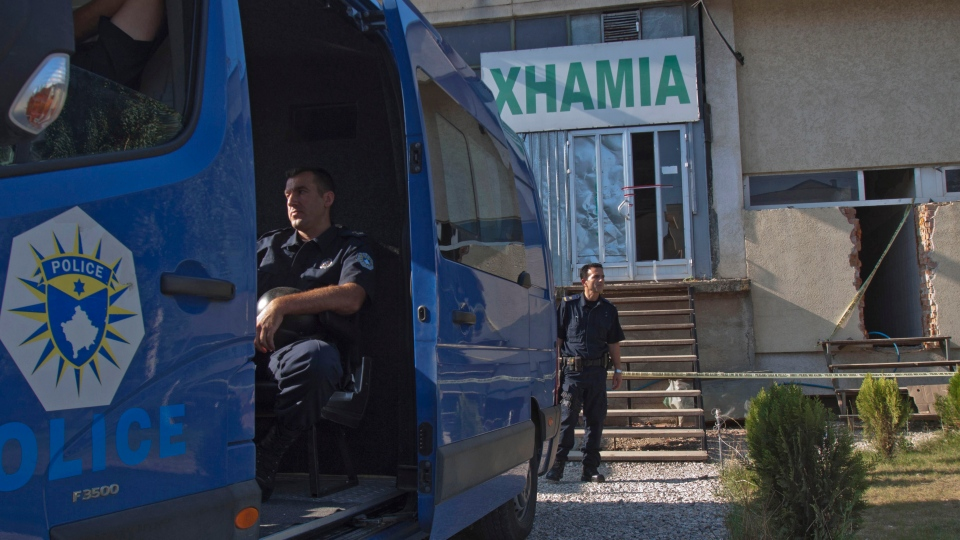 Kosovo police officers guard the entrance of a makeshift mosque after raid in Kosovo capital Pristina on Monday, Aug. 11, 2014.(AP / Visar Kryeziu)