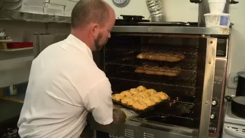 Scott Hoare pulls freshly-baked Pictou County pizza muffins out of the oven at the Coffee Bean in New Glasgow, N.S. (CTV Atlantic)
