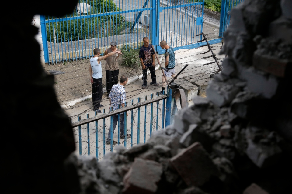 Prisoners are visible through a wall destroyed by shelling at a high-security facility in Donetsk, eastern Ukraine on Monday, Aug. 11, 2014. (AP / Sergei Grits)