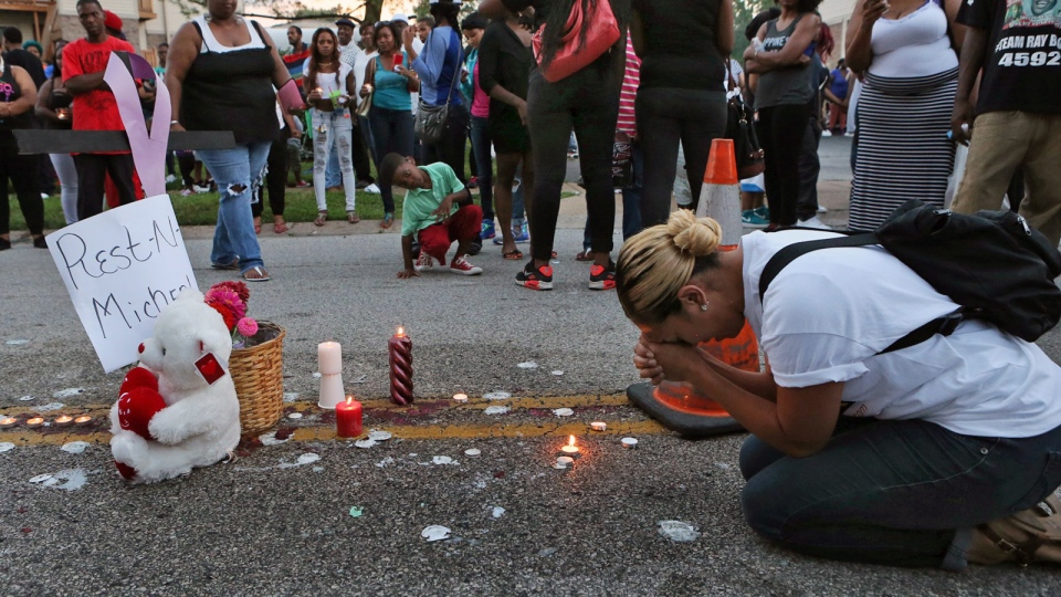Meghan O'Donnell, 29, from St. Louis, prays at the spot where Michael Brown was killed, Sunday evening, Aug. 10, 2014, in Ferguson, Mo. (AP / St. Louis Post-Dispatch, J.B. Forbes)