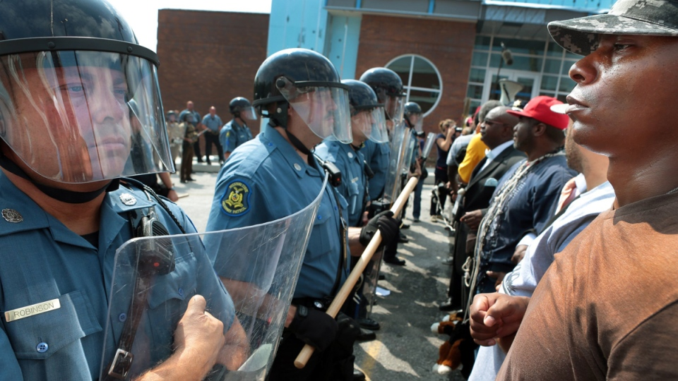 Protestor Boss Bastain of St. Louis locks arms with others as they confront Missouri State Highway Patrol troopers in front of the Ferguson police station on Monday, Aug. 11, 2014. (AP / St. Louis Post-Dispatch, Robert Cohen)