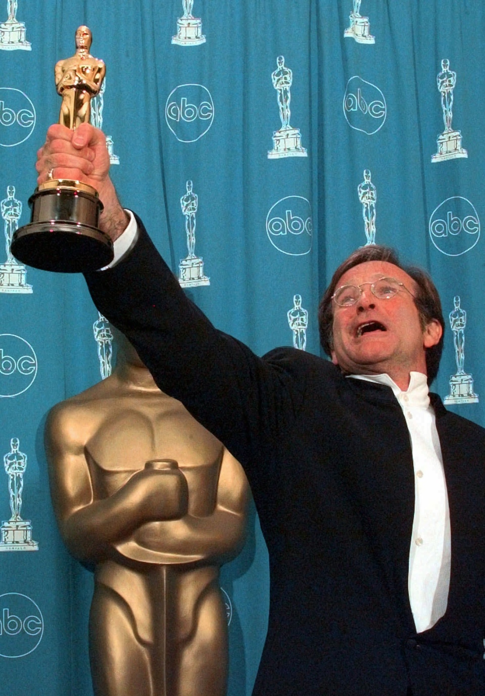 """Robin Williams holding his Oscar high backstage at the 70th Academy Awards at the Shrine Auditorium in Los Angeles after won Best Supporting Actor for """"Good Will Hunting"""" on March 23, 1998. (AP / Reed Saxon)"""