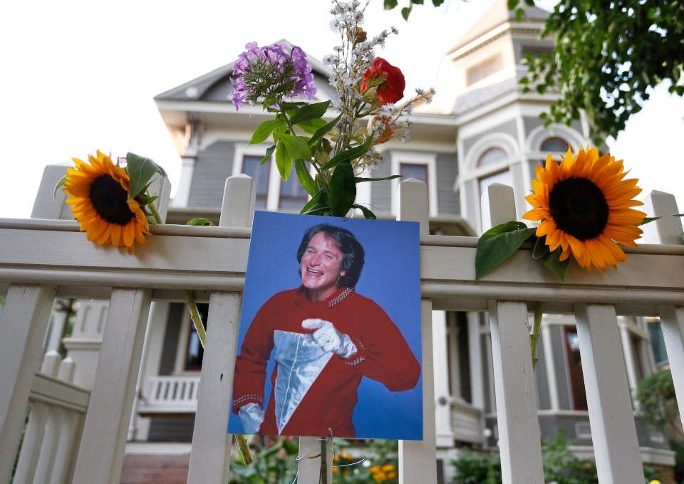 A photo of the late actor Robin Williams as Mork from Ork hangs with flowers left by people paying their respects, in Boulder, Colo., Monday Aug. 11, 2014, at the home where his hit 80's TV series 'Mork and Mindy', was set. (AP / Brennan Linsley)