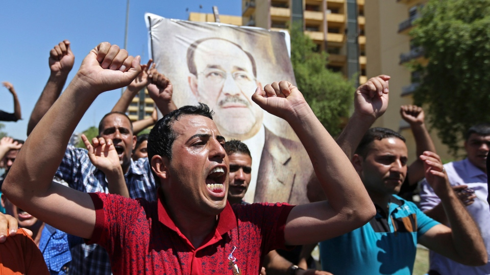 Iraqis chant pro-government slogans and display placards bearing a picture of embattled Prime Minister Nouri al-Maliki during a demonstration in Baghdad, Iraq, Monday, Aug. 11, 2014. (AP / Hadi Mizban)