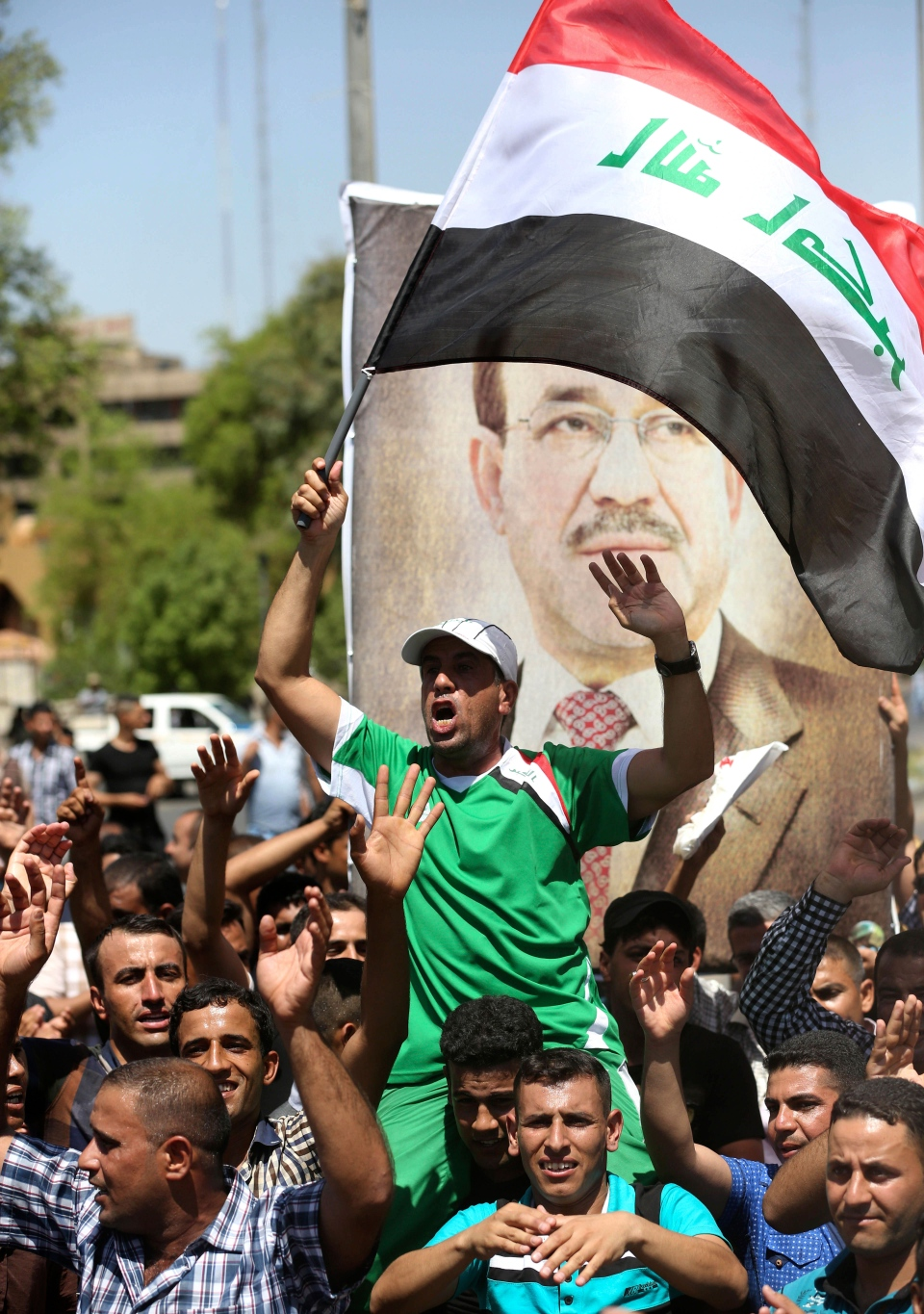 Iraqis chant pro-government slogans and wave national flags to show support for embattled Prime Minister Nouri al-Maliki during a demonstration in Baghdad, Iraq, Monday, Aug. 11, 2014. (AP / Hadi Mizban)