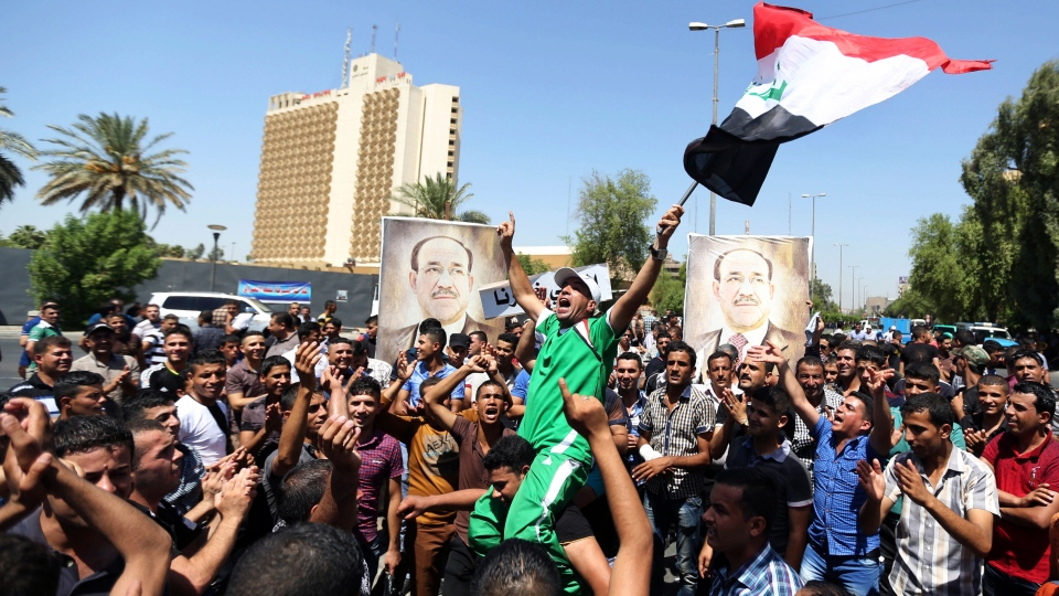 Iraqis chant pro-government slogans and wave national flags in a show of support for embattled Prime Minister Nouri al-Maliki during a demonstration in Baghdad, Iraq, Monday, Aug. 11, 2014. (AP / Hadi Mizban)