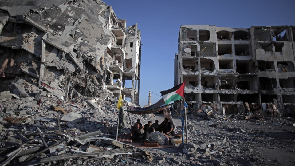 Palestinian Ziad Rizk in a shelter made of a blanket stretched over four boles next to one of the destroyed Nada Towers in the town of Beit Lahiya, Gaza, on Aug. 11, 2014. (AP / Khalil Hamra)