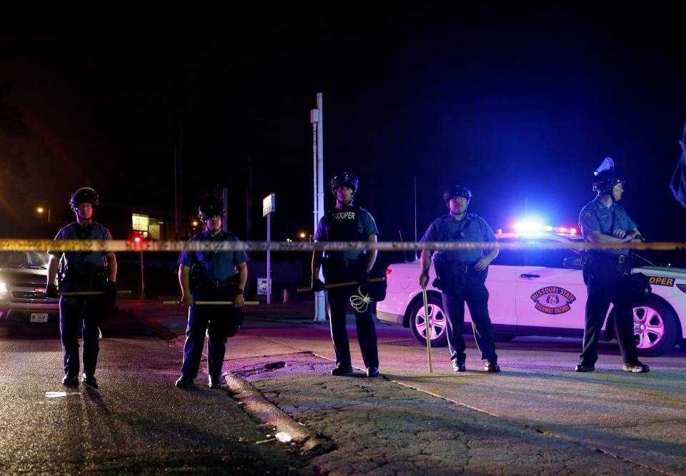 Police wearing riot gear try to disperse a crowd Monday, Aug. 11, 2014, in Ferguson, Mo. (AP / Jeff Roberson)