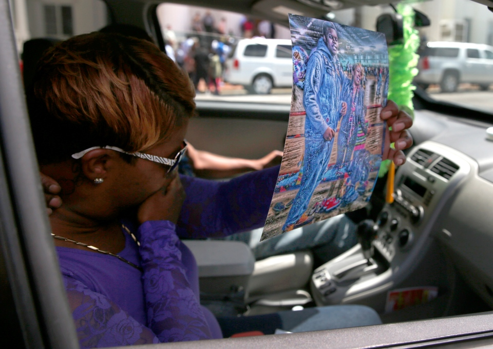 Lesley McSpadden, the mother of Michael Brown Jr., holds up an image of her with her son as she prepares to be driven away from a news conference outside the Old Courthouse on Tuesday, Aug. 12, 2014, in St. Louis. (AP / Jeff Roberson)