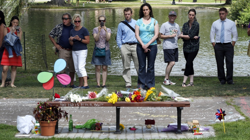 "People pause by a bench at Boston's Public Garden where a small memorial has sprung up at the place where Robin Williams filmed a scene during the movie, ""Good Will Hunting"", Tuesday, Aug. 12, 2014. (AP / Elise Amendola)"