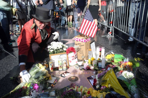 Gregg Donovan places flowers on the star of actor-comedian Robin Williams at a makeshift memorial along the Hollywood Walk of Fame in Los Angeles on Tuesday, Aug. 12, 2014. (AP / Nick Ut)