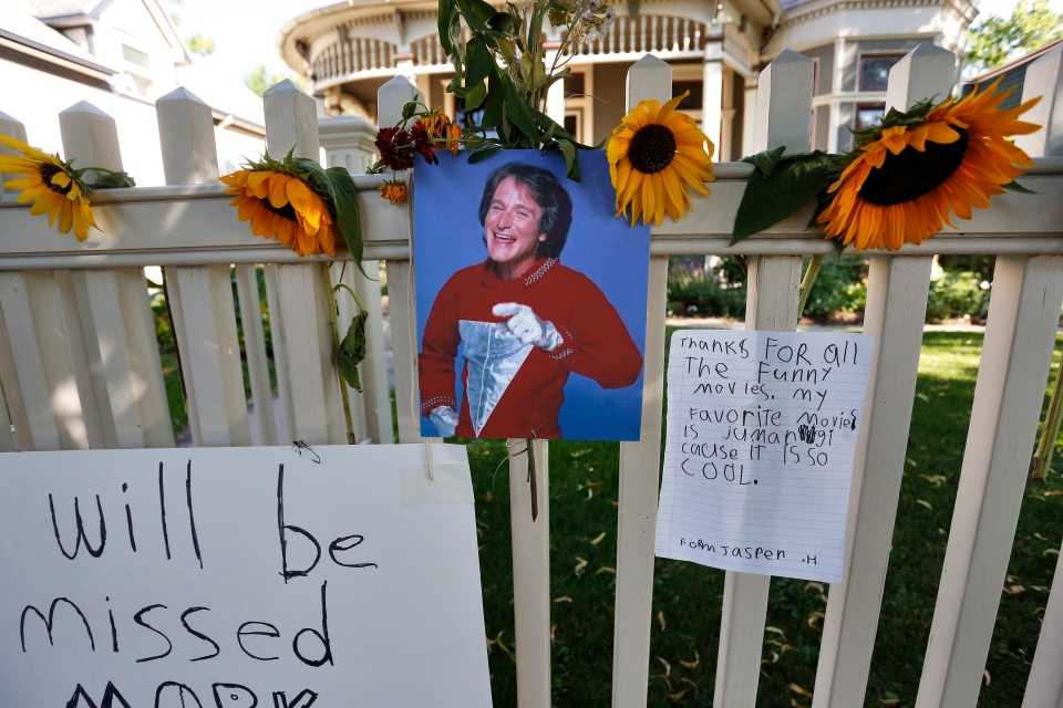 A photo of the late actor Robin Williams playing Mork from Ork hangs with flowers and notes left by people paying their respects, at a makeshift memorial outside the home where the 80s TV series Mork & Mindy, starring Williams, was set, in Boulder, Colo., Tuesday, Aug. 12, 2014. (AP / Brennan Linsley)