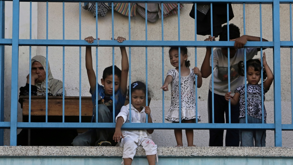 Displaced Palestinian children play on the balcony of the U.N. school where their family sought refuge during the war, in Beit Lahiya, in the northern Gaza Strip, Tuesday, Aug. 12, 2014. (AP / Adel Hana)