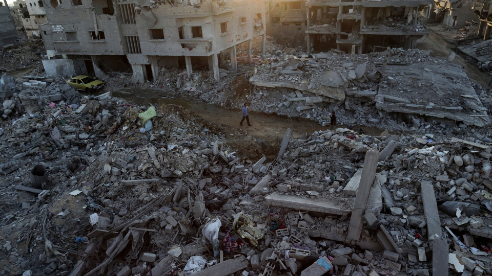 Palestinians walks next the rubble of homes destroyed by Israeli strikes in the town of Beit Hanoun, in the northern Gaza Strip, Tuesday, Aug. 12, 2014. (AP / Adel Hana)
