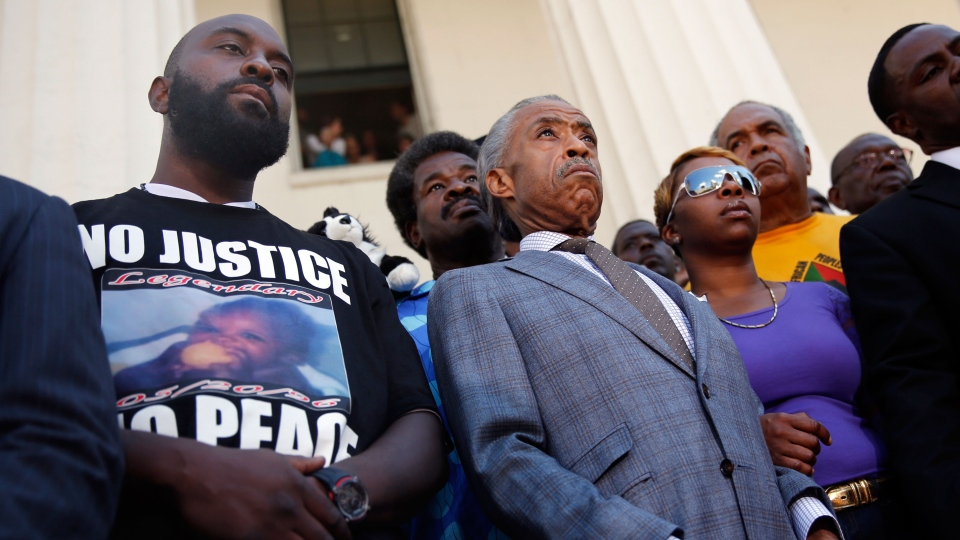 Civil rights leader Rev. Al Sharpton, center, stands with the parents of Michael Brown, Lesley McSpadden, right, and Michael Brown Sr., left, during a news conference outside the Old Courthouse in St. Louis on Tuesday, Aug. 12, 2014. (AP / Jeff Roberson)