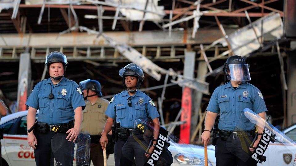 Police wearing riot gear stage outside the remains of a burned convenience store, in Ferguson, Mo. on Monday, Aug. 11, 2014. (AP / Jeff Roberson)