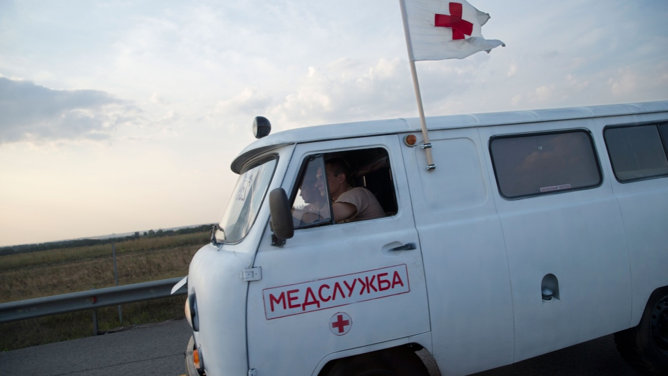 Ambulance car rides in a convoy of white trucks carrying humanitarian aid as it passes along the main road M4 (Don highway) Voronezh region, Russia, Tuesday, Aug. 12, 2014. (AP / Pavel Golovkin)
