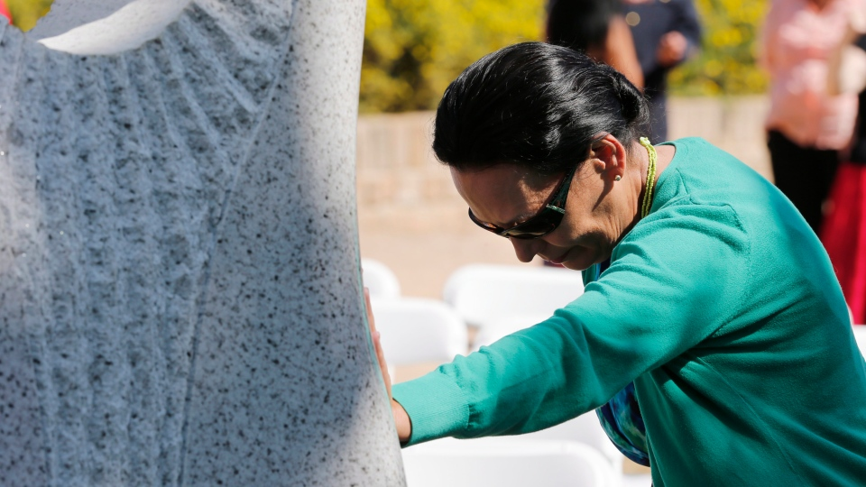 A woman reflects as she places her hand on a monument honouring Manitoba's missing and murdered women and girls which was unveiled in Winnipeg, Tuesday, Aug. 12, 2014. (John Woods / THE CANADIAN PRESS)