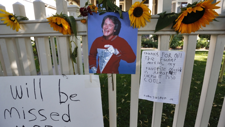 A photo of the late actor Robin Williams playing Mork from Ork hangs with flowers and notes left by people paying their respects, at a makeshift memorial in Boulder, Colo. outside the home where the 80s TV series Mork & Mindy, starring Williams, was set, Tuesday Aug. 12, 2014. (AP / Brennan Linsley)