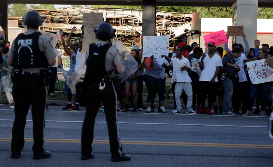 Protesters yell at police Tuesday, Aug. 12, 2014, in Ferguson, Mo. (AP / Jeff Roberson)