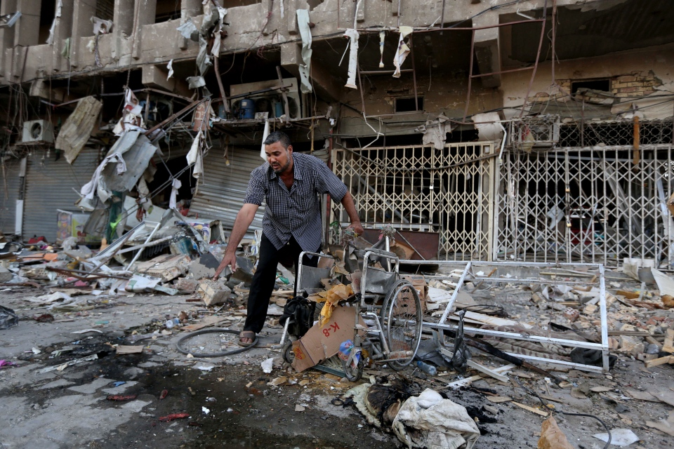 An Iraqi man inspects the site of a car bomb attack in central Baghdad's busy commercial Karradah neighborhood, Iraq, Wednesday, Aug 13, 2014. (AP / Hadi Mizban)