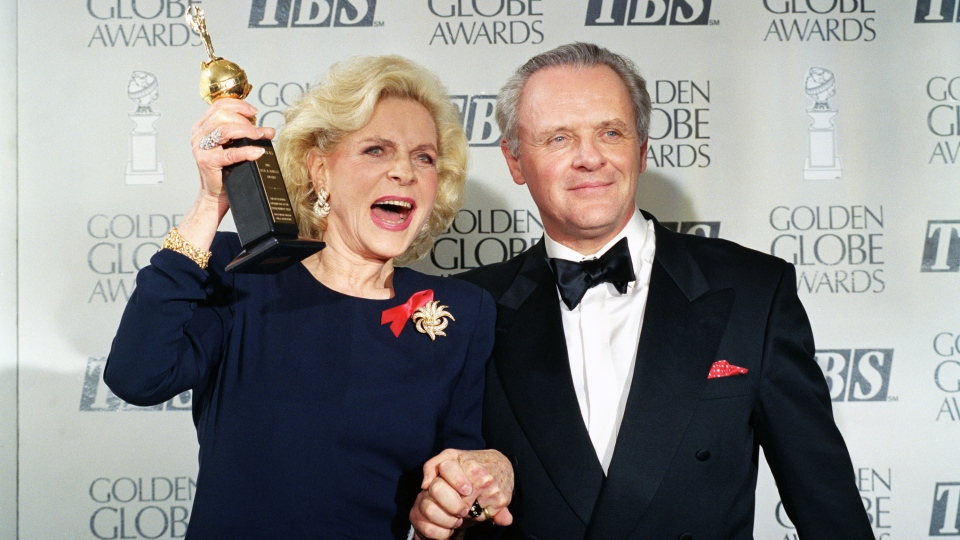 Actress Lauren Bacall holds up her Cecil B. DeMille Award for Lifetime Achievement as she holds hands with actor Anthony Hopkins backstage at the 50th annual Golden Globe Awards in Beverly Hills, Calif. on Jan. 23, 1993. (AP / Reed Saxon)