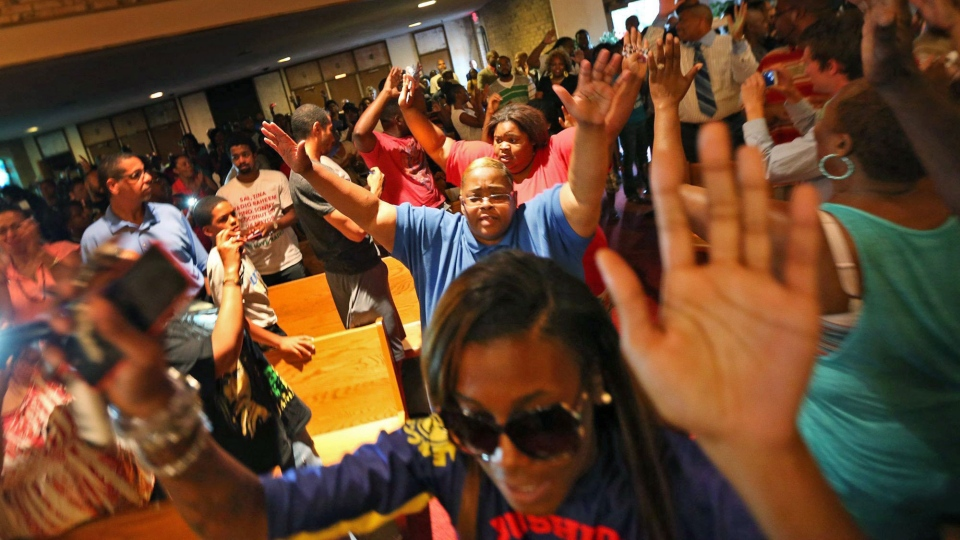 A group of young protestors left the QuikTrip area, walked to the Greater St. Mark Missionary Baptist Church to join a gathering with Michael Brown's family and Rev. Al Sharpton. They entered the church chanting, 'Hands up, don't shoot' on Tuesday, Aug. 12, 2014, in Dellwood. (St. Louis Post-Dispatch, Chris Lee)